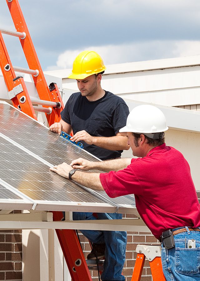 Two electricians installing commercial solar panels